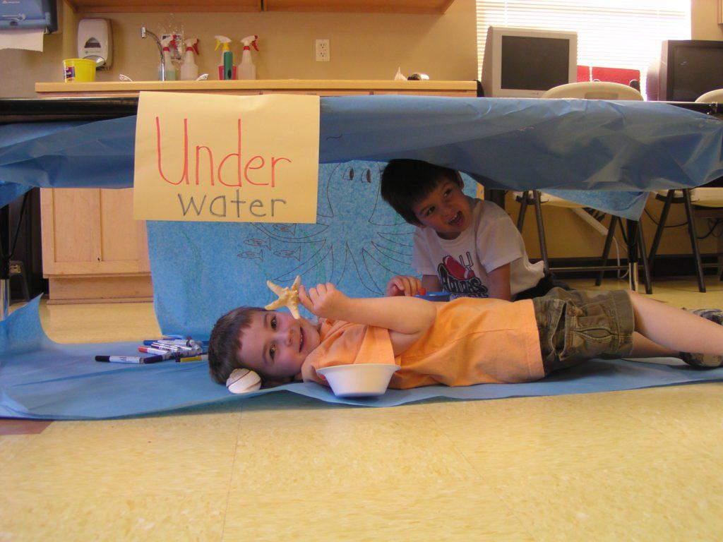 boys holding sea creatures under a table at a Preschool & Daycare Serving San Antonio, TX