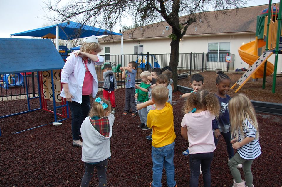children and teacher playing outside at a Preschool & Daycare Serving San Antonio, TX