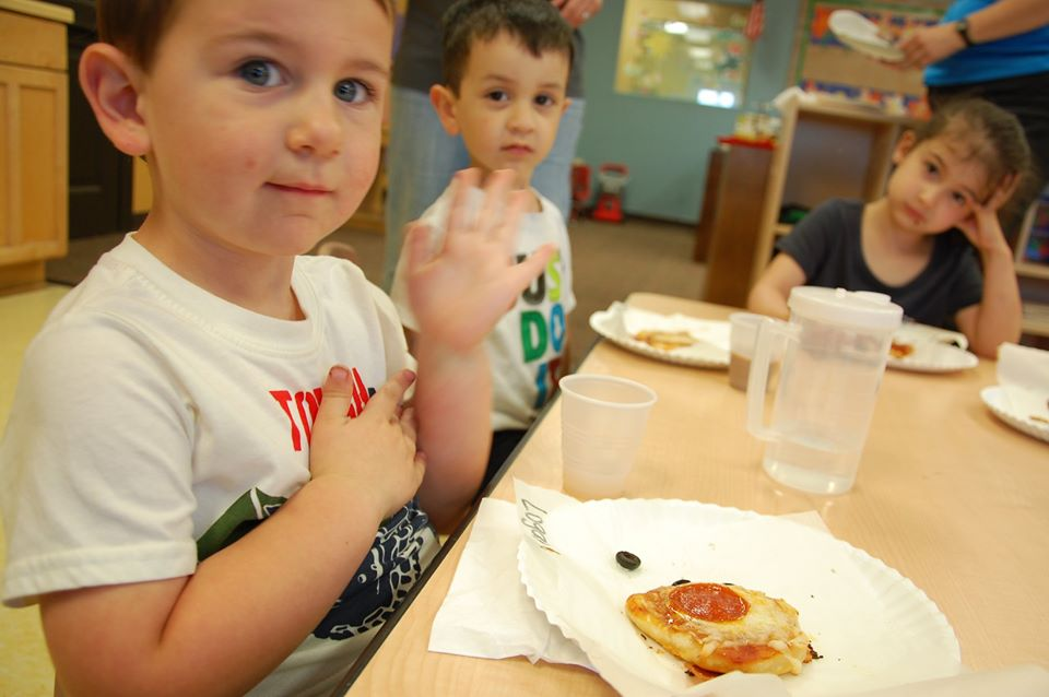 children sitting at a table eating food at a Preschool & Daycare Serving San Antonio, TX