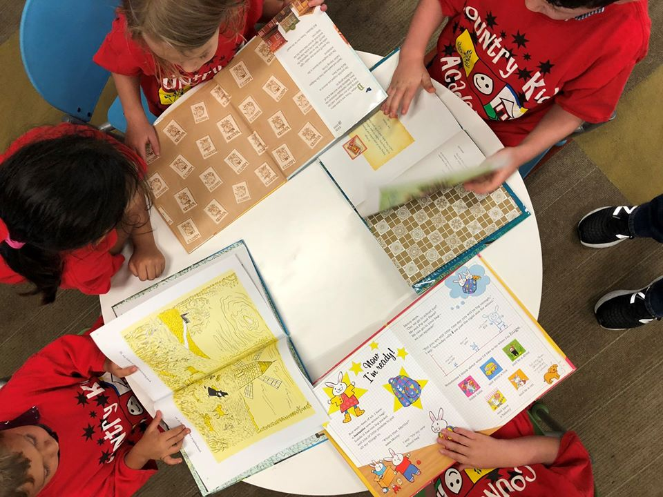 children sitting at a table reading picture books at a Preschool & Daycare Serving San Antonio, TX