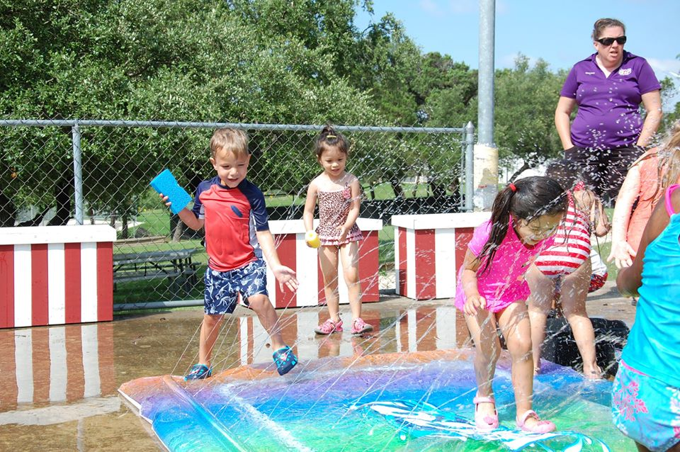 kids enjoying fun in the sun with splash pad at a Preschool & Daycare Serving San Antonio, TX
