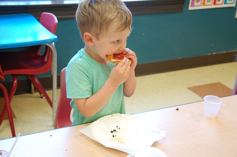 little boy eating pizza at a Preschool & Daycare Serving San Antonio, TX