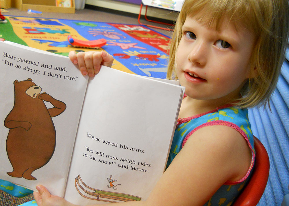 little girl showing off picture book at a Preschool & Daycare Serving San Antonio, TX