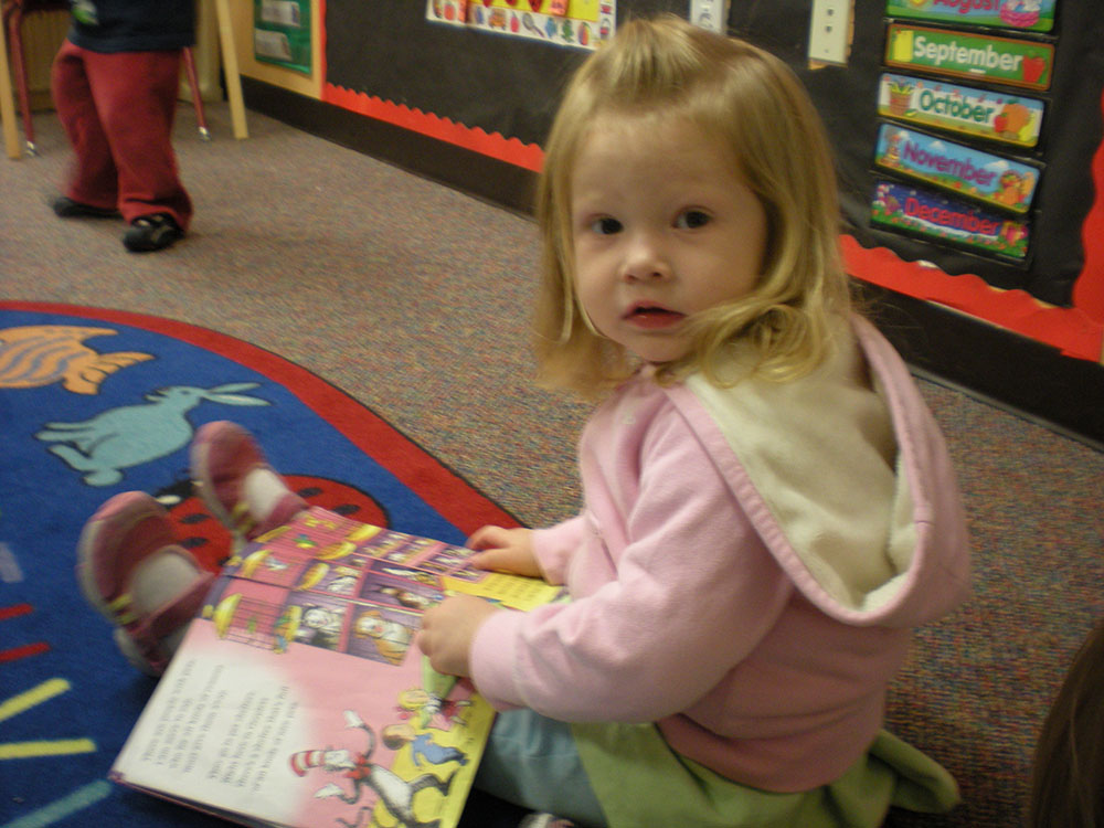 little girl sitting with a picture book at a Preschool & Daycare Serving San Antonio, TX