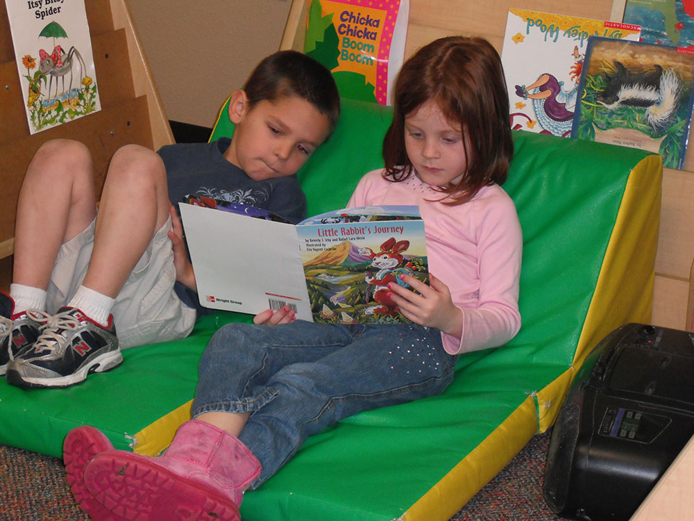 preschool boy & girl reading book at a Preschool & Daycare Serving San Antonio, TX
