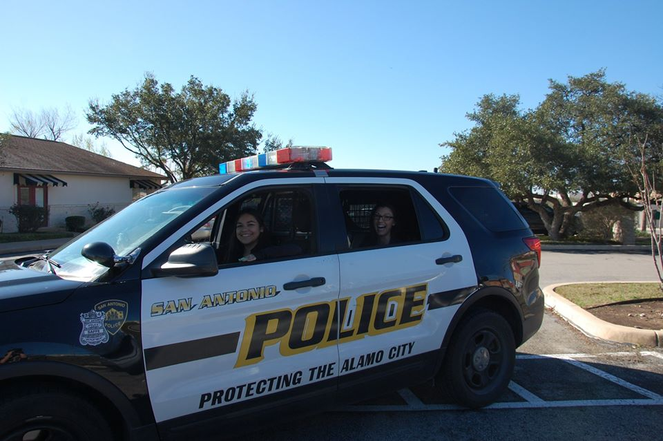 smiling teachers inside police car at a Preschool & Daycare Serving San Antonio, TX