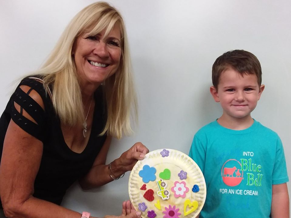 teacher and boy showing off art in class at a Preschool & Daycare Serving San Antonio, TX
