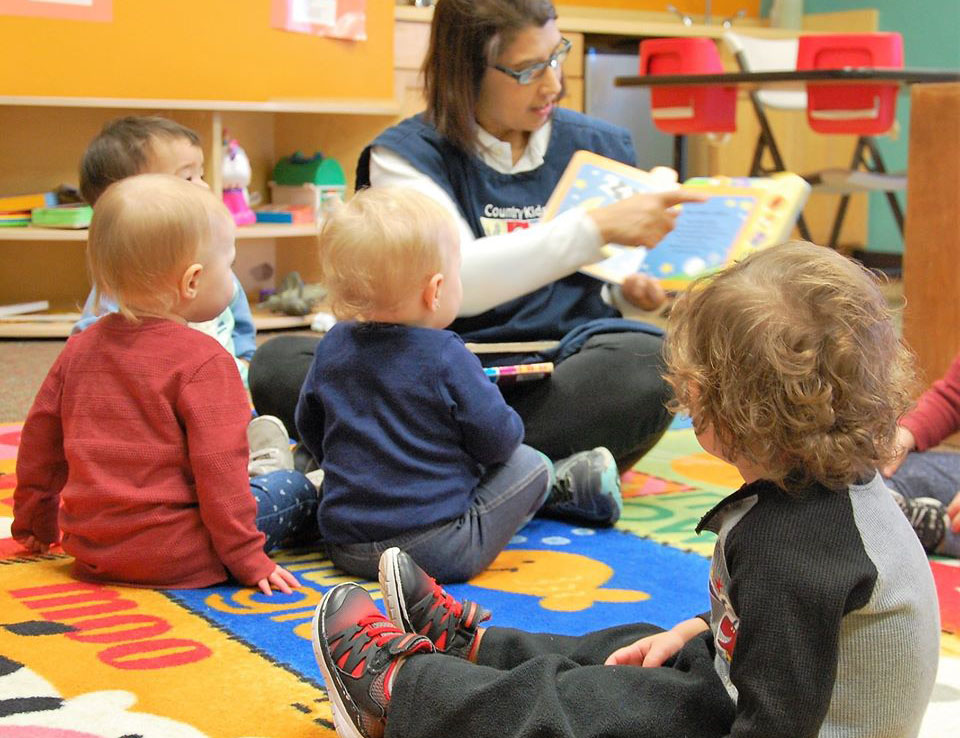 teacher reading to toddlers in class at a Preschool & Daycare Serving San Antonio, TX