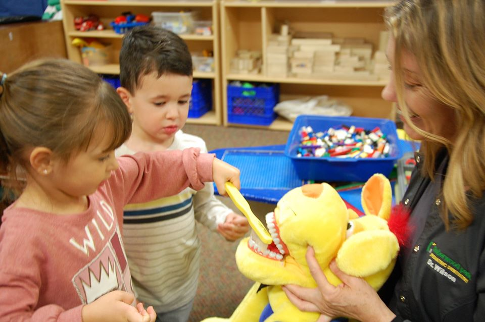 teacher showing preschool children oral health at a Preschool & Daycare Serving San Antonio, TX