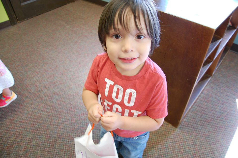 young boy holding bag and smiling at a Preschool & Daycare Serving San Antonio, TX