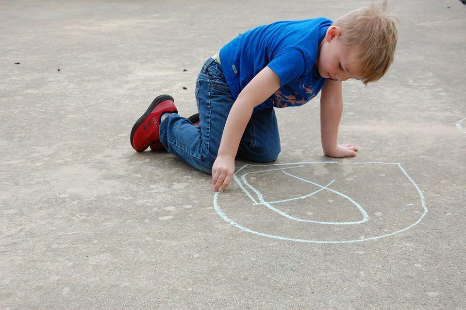young boy writing with chalk on sidewalk at a Preschool & Daycare Serving San Antonio, TX